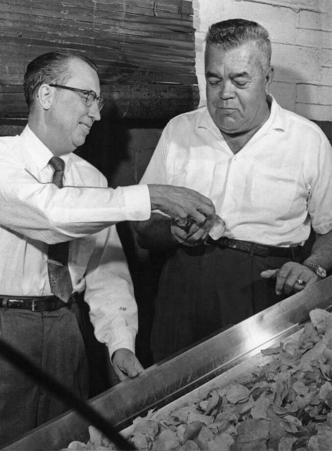 Arthur B. Preble, left, hands a potato chip off the line to George W. Dentler at the Dentler Maid potato chip factory in Houston in 1963. In 1931, Preble partnered with Dentler's father, George H. Dentler, in the family-run business which George H. started around 1910. Photo: Owen Johnson, HP Staff / Houston Chronicle