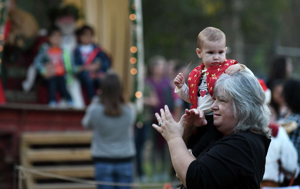 Gisele Nash, of Cypress, and her granddaughter Abigail, 1, enjoy the songs of the Kingwood High School Madrigals during the Old-Fashioned Christmas at the Jesse H. Jones Park & Nature Center in Humble on Dec. 2, 2017. (Photo by Jerry Baker/Freelance)