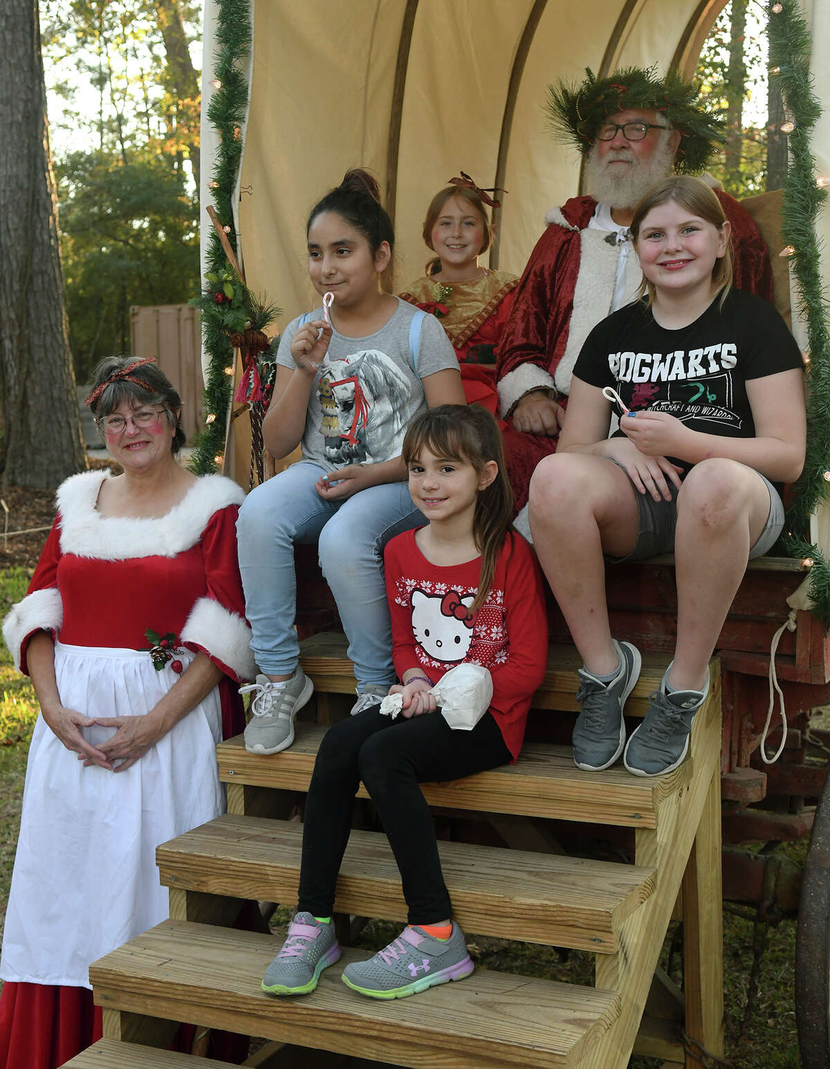 Saint Nicholas (Joe Nelson of Humble), top right, with Mrs. Nicholas (Joe's wife Elaine Nelson), bottom left, and their elf Lillian Monarch, 8, back center, of Conroe, share a photo with Josie Gamez, 10, center left, Kendall Cawood, 9, front right, and Caylin McClellan, 10, center right, all from Cypress, in a covered wagon during the Old-Fashioned Christmas at the Jesse H. Jones Park & Nature Center in Humble on Dec. 2, 2017. (Photo by Jerry Baker/Freelance)