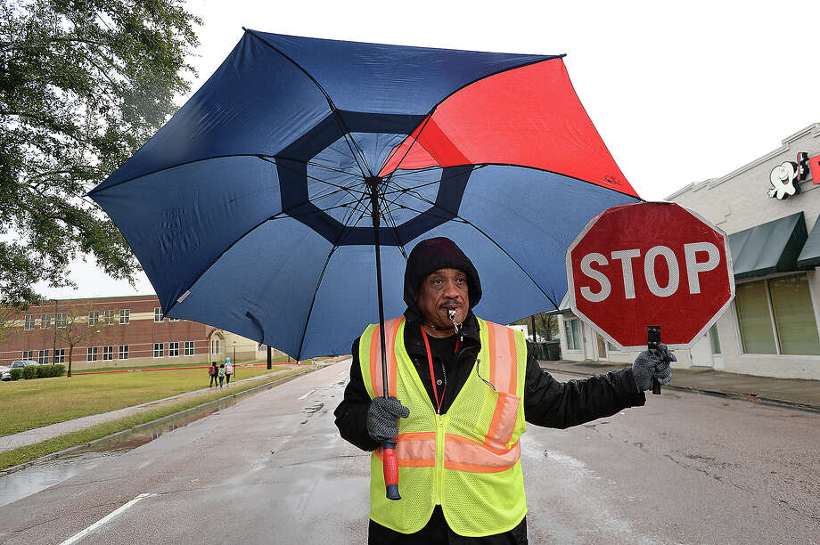Albert Barry, who has been working as a crossing guard for six years, keeps cover from afternoon rain showers as he assists students at  Pietzsch MacArthur Elementary School make their way across Highland Avenue after school Wednesday. Barry bundled up in three layers, a hat and gloves to try and keep warm as temperatures fell and wind and rain continued to add to the wintry conditions. Between school start and dismissal, Barry's duties kept him outside in the elements for roughly three hours. Temperatures are expected to remain low or dip down further throughout the remainder of the week, with snow possibly in the forecast for Friday. Photo taken Wednesday, December , 2017 Kim Brent/The Enterprise Photo: Kim Brent / BEN