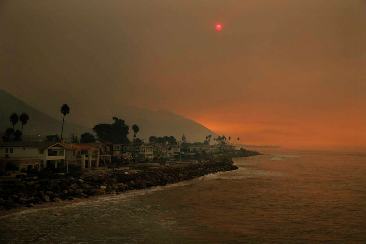 Homes stand along the beach as the sun is visible through thick smoke from a wildfire Wednesday, Dec. 6, 2017, in Ventura, Calif. A dramatic new wildfire erupted in Los Angeles early Wednesday as firefighters battled three other destructive blazes across Southern California. (AP Photo/Jae C. Hong)