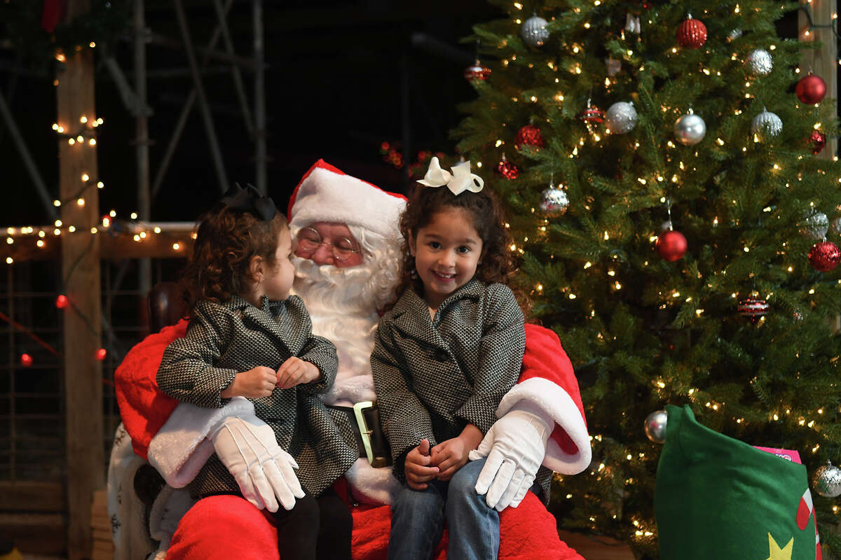 Lincoln Blackman, 2, left, and her sister Charlie, 4, the daughters of Chuck and Cindy Blackman of Atascocita, visit with Santa, the dad of Kingwood Park High School junior and FFA member Avery Rose, during the annual KHS & KPHS FFA Santa's Farm event at the Kingwood Ag Barns on Dec. 1, 2017. (Photo by Jerry Baker/Freelance)