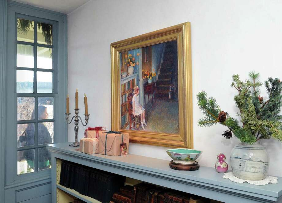 "A Childe Hassam 1912 oil painting titled ""Clarissa"" can be seen above a shelf decorated with Christmas presents and evergreen branches in the Bush-Holley House that is now decorated for Christmas in the Cos Cob section of Greenwich, Conn., Wednesday, Dec. 6, 2017. Greenwich Historical Society experts, used historically accurate decorations and staging to achieve the Christmas decor during the Holley family's era. Photo: Bob Luckey Jr. / Hearst Connecticut Media / Greenwich Time"