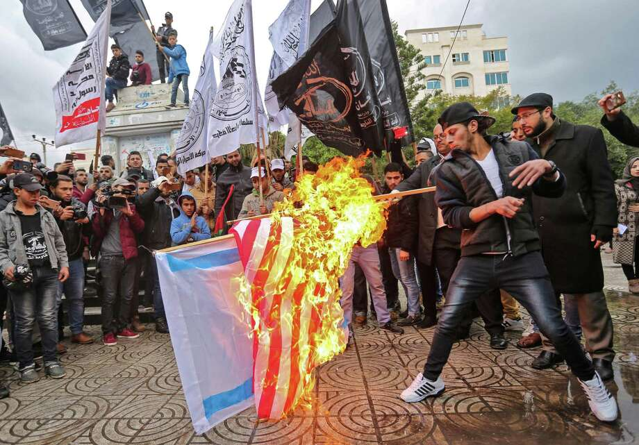 Palestinian protesters burn the US and Israeli flags in Gaza City on December 6, 2017. President Donald Trump is set to recognise Jerusalem as Israel's capital, upending decades of careful US policy and ignoring dire warnings from Arab and Western allies alike of a historic misstep that could trigger a surge of violence in the Middle East. / AFP PHOTO / MAHMUD HAMSMAHMUD HAMS/AFP/Getty Images Photo: MAHMUD HAMS, Contributor / AFP/Getty Images / AFP or licensors