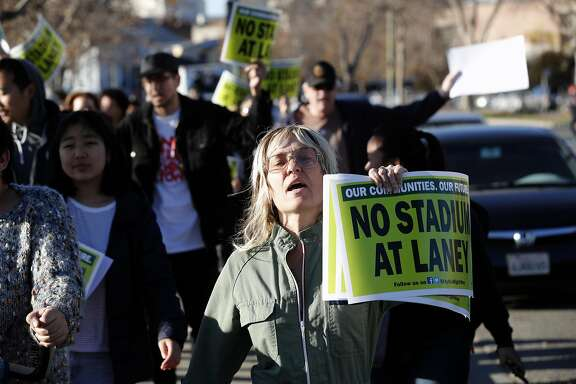 Students and faculty members of Laney College join with community activists, and nearby resident Katy Bell, (right) on Wednesday December 6, 2017, as they march to the Peralta Community College District offices to demand a meeting with Chancellor Jowel Laquerre to talk about the future plans of building a baseball stadium for the Oakland Athletics, in downtown Oakland, Calif.