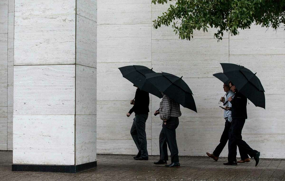 Pedestrians stroll past Jones Hall in the rain on Wednesday as a cold front barged into Houston, making it feel more wintry.