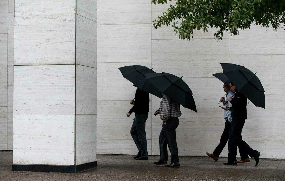 Pedestrians stroll past Jones Hall in the rain on Wednesday as a cold front barged into Houston, making it feel more wintry.  Photo: Brett Coomer, Staff / © 2017 Houston Chronicle