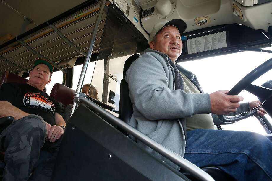Christopher Martinez takes the wheel for a practice run in a bus as fellow student Donnie Piper looks on at the Academy of Truck Driving in Oakland. Photo: Liz Hafalia, The Chronicle