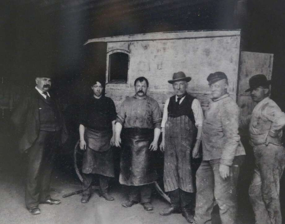 George V. Arth (left) is seen in a reprint of a 1902 archival photo displayed in the Oakland auto body repair shop he founded. Photo: Lea Suzuki, The Chronicle