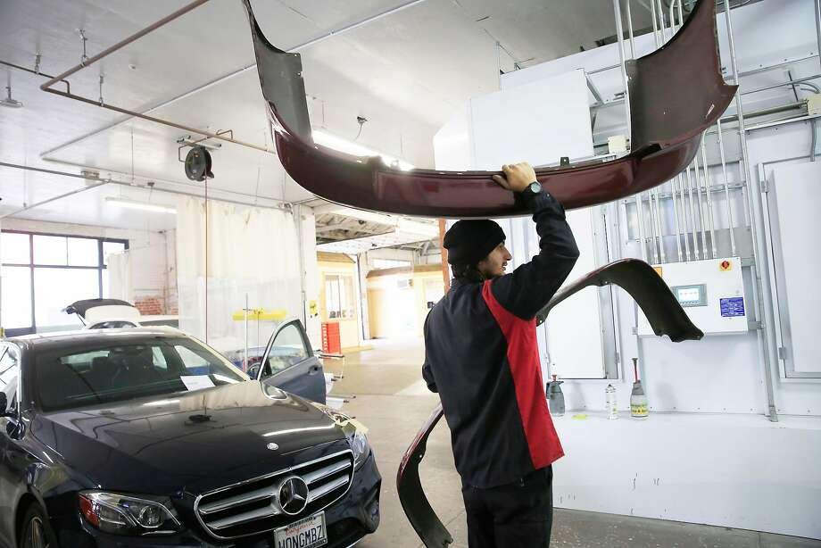 Technician Julio Saucedo carries parts through the George V. Arth & Son body shop in Oakland. The shop has adopted new technology as the industry changes. Photo: Lea Suzuki, The Chronicle