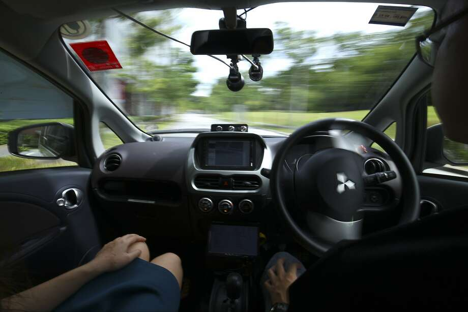 A driver in Singapore takes his hands off the wheel as he tests a NuTonomy vehicle in Singapore. The company operates self-driving taxis in that city and recently began offering the service in Boston. Photo: Yong Teck Lim, AP
