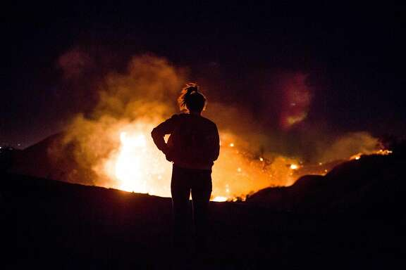A resident watches as the Creek Fire burns along a hillside near homes in the Shadow Hills neighborhood of Los Angeles, California, on December 5, 2017. More than a thousand firefighters were struggling to contain a wind-whipped brush fire in southern California on December 5 that has left at least one person dead, sent thousands fleeing, and was choking the area with thick black smoke. / AFP PHOTO / Kyle GrillotKYLE GRILLOT/AFP/Getty Images