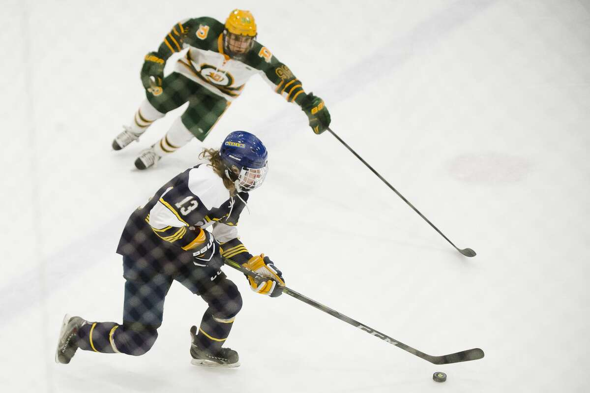 Midland junior Travis Grimaldi moves the puck down the ice as Dow sophomore Luke Blasy follows behind during their game on Wednesday, Dec. 6, 2017 at the Midland Civic Arena. (Katy Kildee/kkildee@mdn.net)