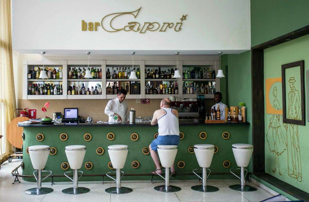 FILE - In this Sept. 12, 2017, file photo, a customer sits at the lobby bar of the Hotel Capri in Havana, Cuba. Doctors treating the U.S. Embassy victims of mysterious, invisible attacks in Cuba have discovered brain abnormalities as they search for clues to hearing, vision, balance and memory damage, The Associated Press has learned. Physicians, FBI investigators and U.S. intelligence agencies have spent months trying to piece together the puzzle in Havana, where the U.S. says 24 government officials and spouses fell ill starting last year in homes and later in some hotels. (AP Photo/Desmond Boylan)