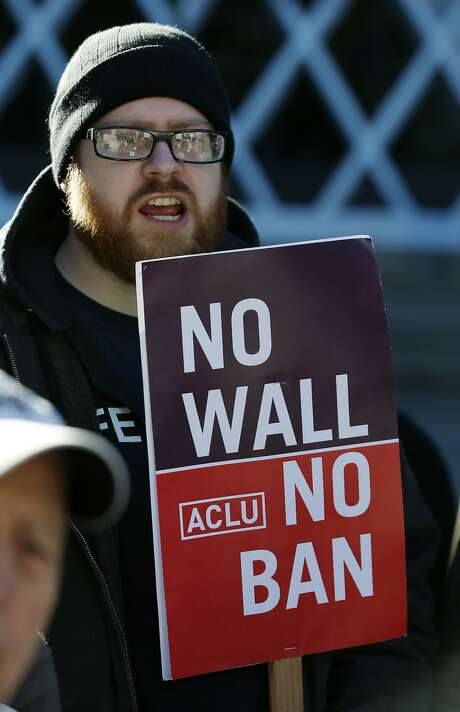 """Eric Buerk, of Seattle, holds a sign that reads """"No Wall No Ban,"""" during a protest, Wednesday, Dec. 6, 2017, outside a federal courthouse in Seattle. The U.S. Supreme Court decision allowing President Donald Trump's third travel ban to take effect has intensified the attention on a legal showdown Wednesday before three judges in Seattle who have been cool to the policy as they hear arguments in Hawaii's challenge to the ban, which restricts travel to the United States by residents of six mostly Muslim countries and has been reviled by critics as discriminatory. (AP Photo/Ted S. Warren) Photo: Ted S. Warren, Associated Press"""