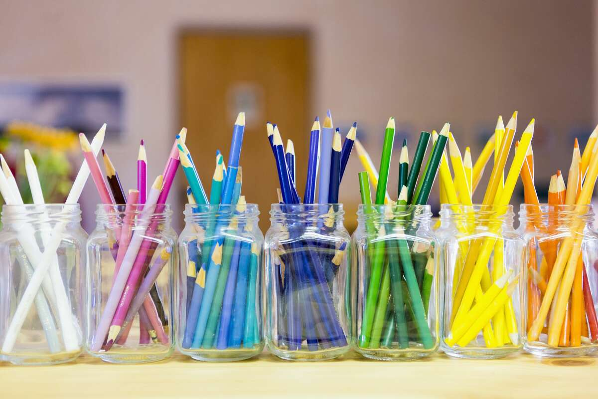 Close up of multicolor pencils organized in jars in a classroom.