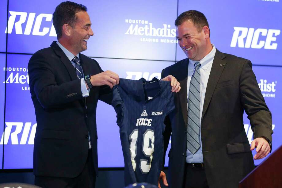 Rice athletic director Joe Karlgaard, left, offers a wardrobe option to new Owls football coach Mike Bloomgren on Wednesday. Bloomgren listed Rice, Stanford, Northwestern, Duke and Vanderbilt, all noted for academics, as his desirable destinations. Photo: Michael Ciaglo, Houston Chronicle / Michael Ciaglo