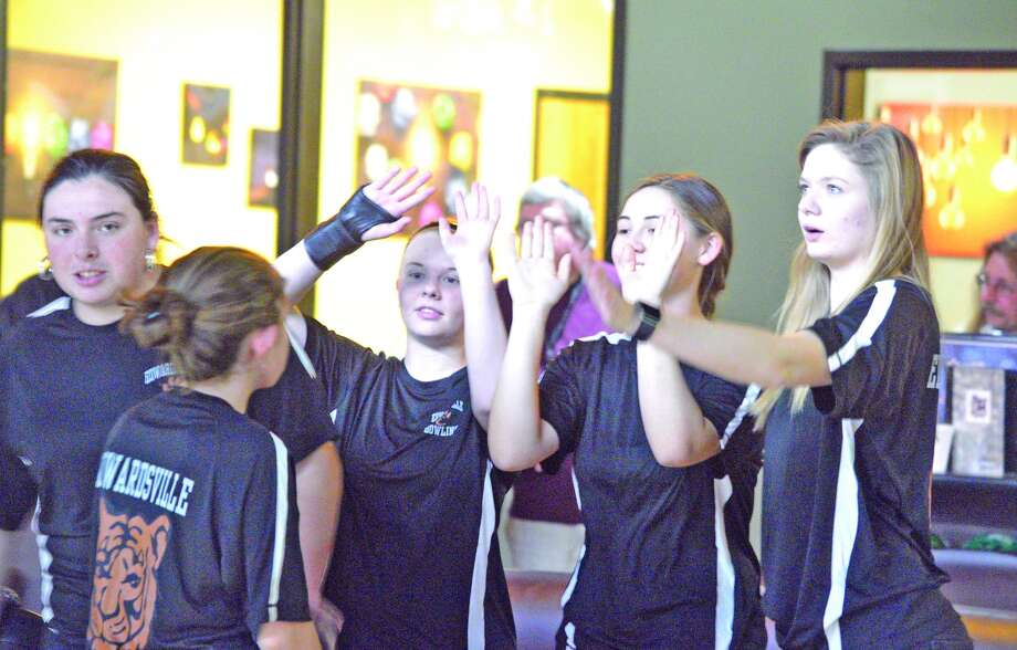 The Edwardsville girls' bowling celebrates a strike during Wednesday's match against Alton.