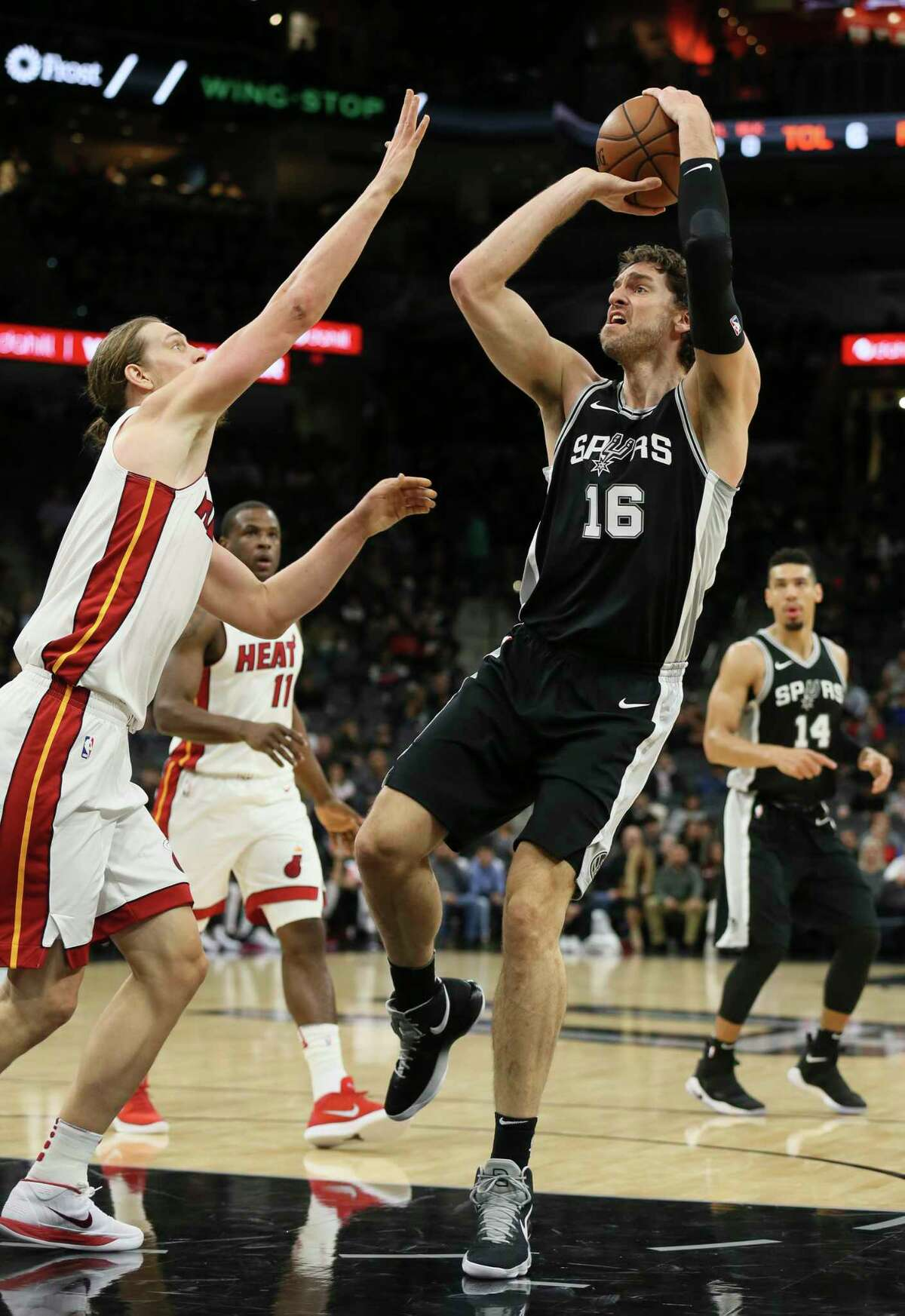 Spurs' Pau Gasol (16) attempts a shot against Miami Heat's Kelly Olynyk (09) at the AT&T Center on Wednesday, Dec. 6, 2017.