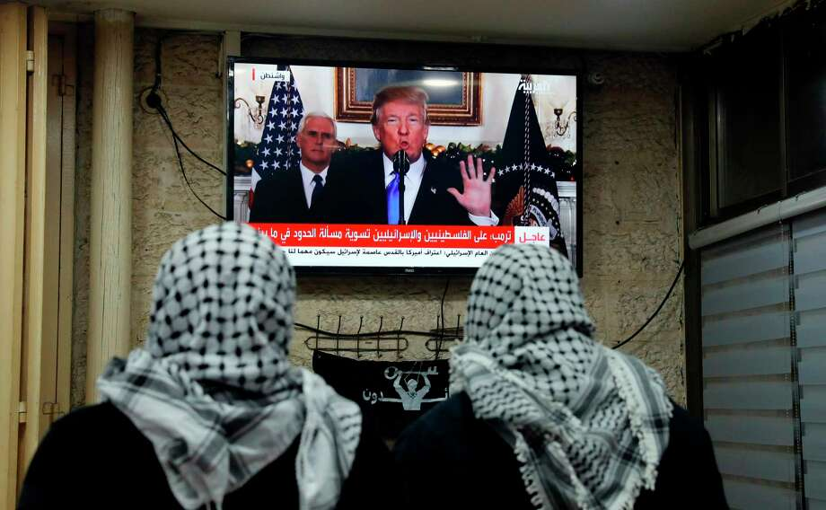 Palestinian men watch an address given by President Donald Trump at a cafe in Jerusalem on Wednesday. Photo: AHMAD GHARABLI, Contributor / AFP or licensors