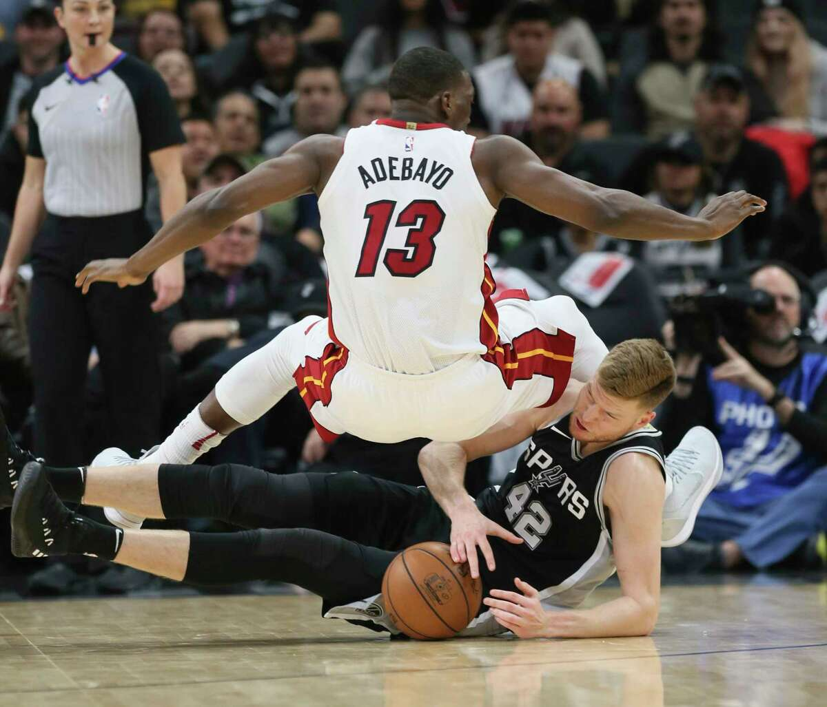 Spurs' Davis Bertans (42) dives for a loose ball against Miami Heat's Bam Adebayo (13) at the AT&T Center on Wednesday, Dec. 6, 2017.