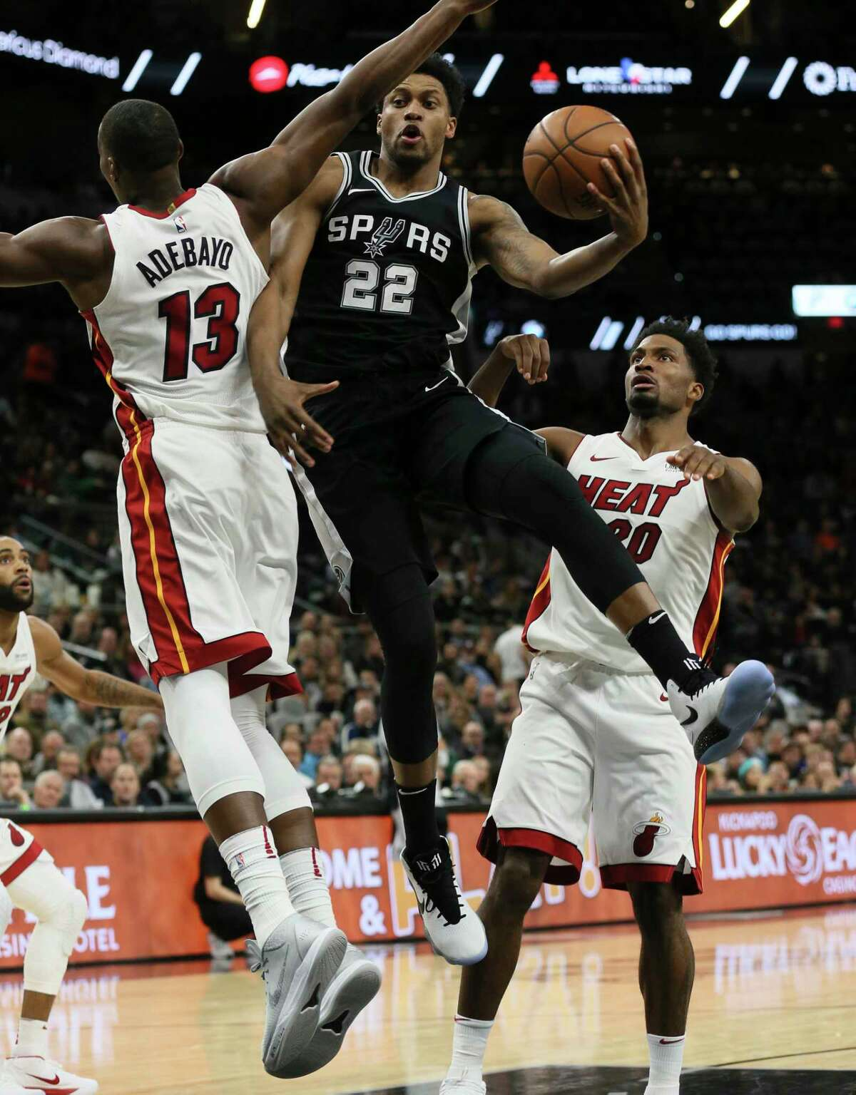 Spurs' Rudy Gay (22) makes a pass while driving between Miami Heat's Bam Adebayo (13) and Justise Winslow (20) at the AT&T Center on Wednesday, Dec. 6, 2017.