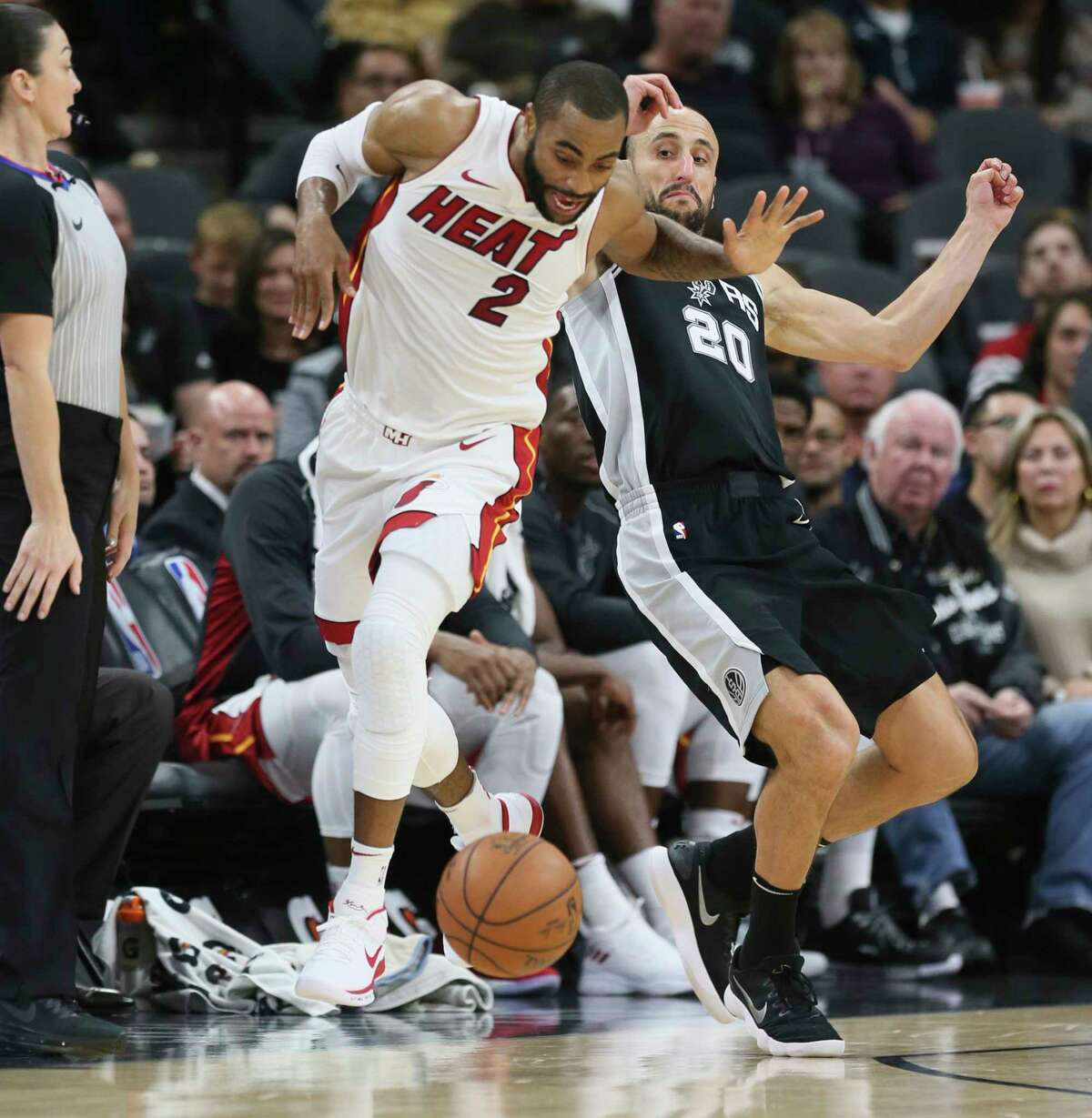 Spurs' Manu Ginobili (20) draws an offensive foul against Miami Heat's Wayne Ellington (02) at the AT&T Center on Wednesday, Dec. 6, 2017.