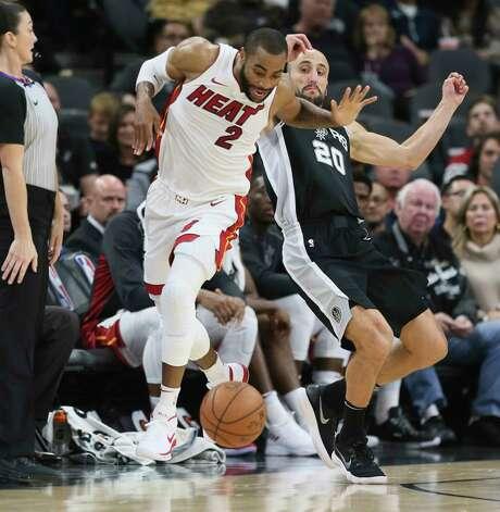 Spurs' Manu Ginobili (20) draws an offensive foul against Miami Heat's Wayne Ellington (02) at the AT&T Center on Wednesday, Dec. 6, 2017. Photo: Kin Man Hui, San Antonio Express-News / ©2017 San Antonio Express-News