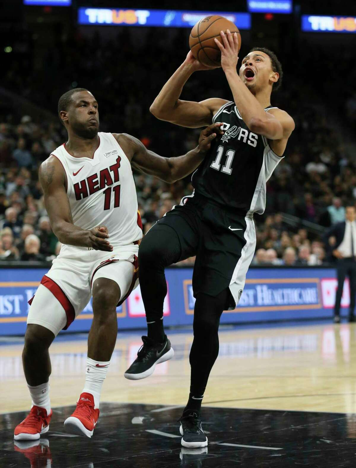 Spurs' Bryn Forbes (11) draws contact as he score against Miami Heat's Dion Waiters (11) at the AT&T Center on Wednesday, Dec. 6, 2017.