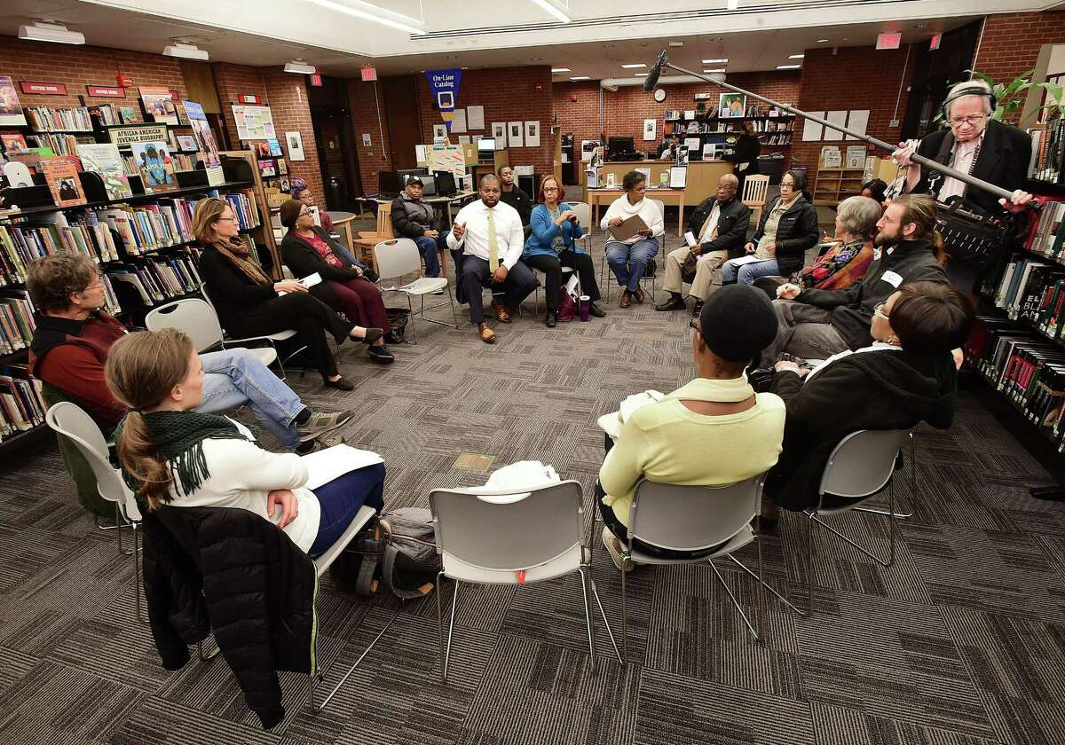 State Sen. Gary Winfield, top center, speaks during a community conversation Wednesday at the Stetson Branch Library in New Haven.