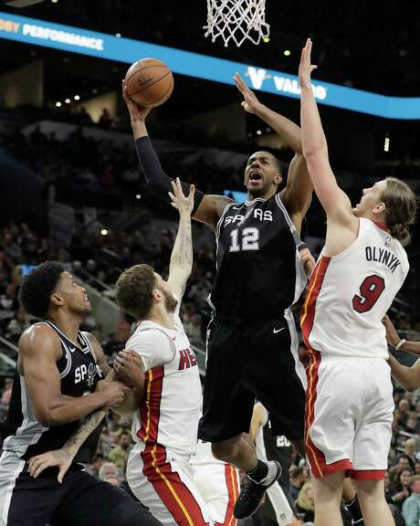 San Antonio Spurs forward LaMarcus Aldridge (12) shoots over Miami Heat defenders Kelly Olynyk (9) and Tyler Johnson (8) during the second half of an NBA basketball game, Wednesday, Dec. 6, 2017, in San Antonio. San Antonio won 117-105. (AP Photo/Eric Gay) Photo: Eric Gay, Associated Press / Copyright 2017 The Associated Press. All rights reserved.