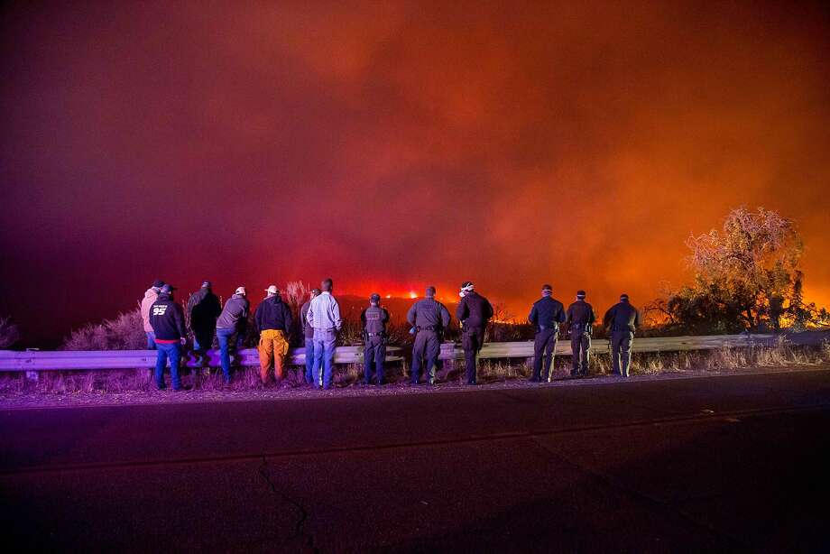 Police and Fire crews watch as the Thomas Fire burns a hillside in Ojai, California, December 7, 2017. Local emergency officials warned of powerful winds on Thursday that will feed wildfires raging in Los Angeles, threatening multi-million dollar mansions with blazes that have already forced more than 200,000 people to flee.  Photo: KYLE GRILLOT, AFP/Getty Images
