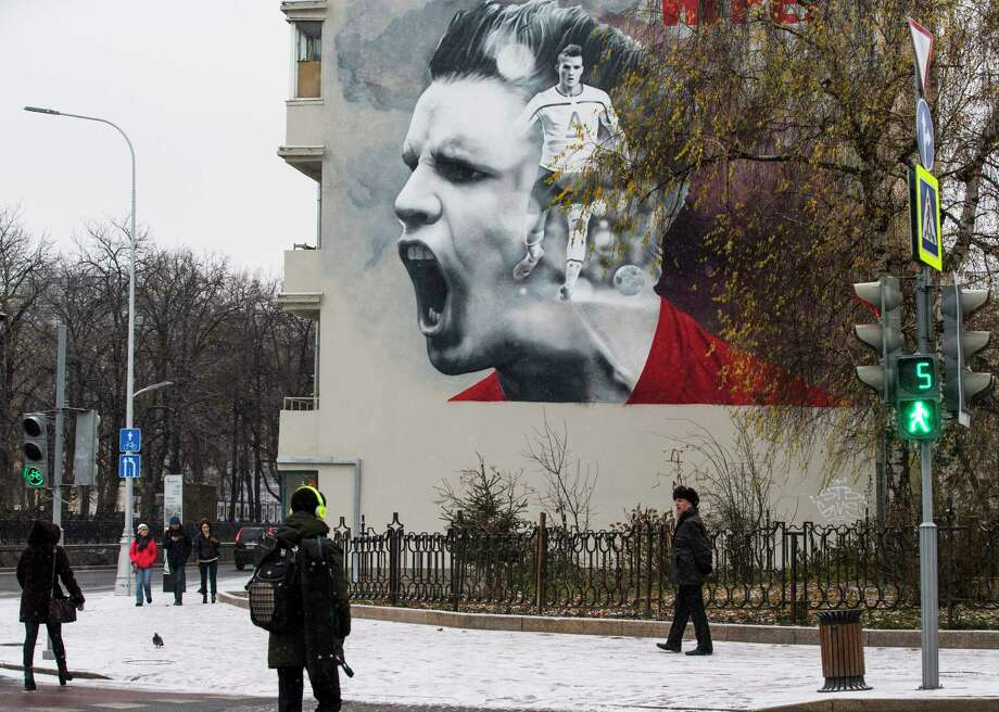 People walk past a huge poster promoting the upcoming soccer World Cup 2018 tournament in Moscow, Russia, Tuesday, Nov. 28, 2017. The World Cup will be played at 12 stadiums in 11 Russian cities. (AP Photo/Alexander Zemlianichenko) Photo: Alexander Zemlianichenko, STF / AP