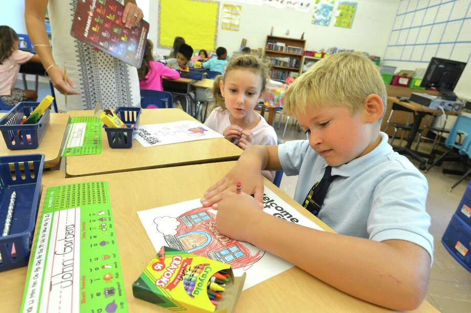 Risa davis and John Garbera get to coloring on the first day of classes at Wolfpit Elementary School on Wednesday, Aug. 30. The Norwalk Board of Education unanimously approved a Memorandum of Understanding with the Norwalk Federation of Teachers Tuesday night that will increase the elementary school day by 30 minutes next year. Photo: Alex Von Kleydorff / Hearst Connecticut Media / Norwalk Hour