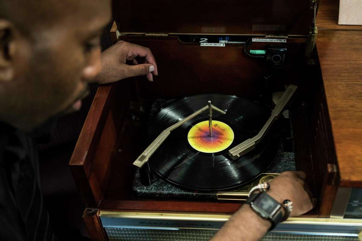 DeAndre Hargrove demonstrates the use of the vinyl record listening room at Aris Market Square on Wednesday, Dec. 6, 2017, in Houston.