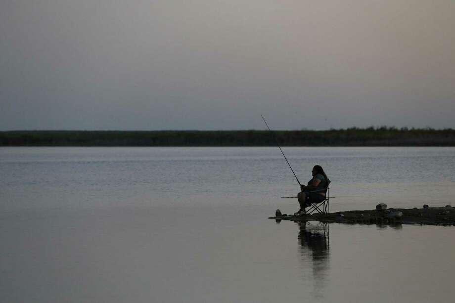A woman tries you luck while fishing at Falcon Lake in Zapata, Texas, Sunday, April 30, 2017. Photo: JERRY LARA / San Antonio Express-News / © 2017 San Antonio Express-News