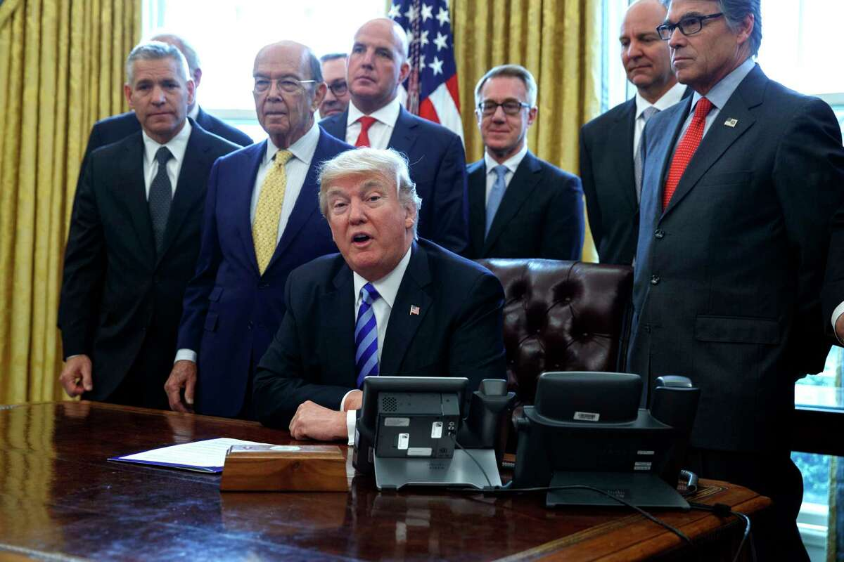 FILE - In this March 24, 2017, file photo, President Donald Trump announces the approval of a permit to build the Keystone XL pipeline, clearing the way for the $8 billion project in the Oval Office of the White House in Washington. From left are, TransCanada CEO Russell K. Girling, Commerce Secretary Wilbur Ross and Energy Secretary Rick Perry. Amid staff turmoil and shake-ups, travel bans blocked by federal courts and the Russia cloud hanging overhead, Trump is plucking away at another piece of his agenda: undoing Obama. (AP Photo/Evan Vucci)