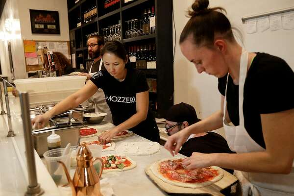 In this Nov. 5, 2015 photo, Mozzeria owner Melody Stein, left, and Sabrina Ferguson makes pizzas at the restaurant in San Francisco. Mozzeria owners Russ and Melody Stein as well as staff workers are deaf. (AP Photo/Jeff Chiu)