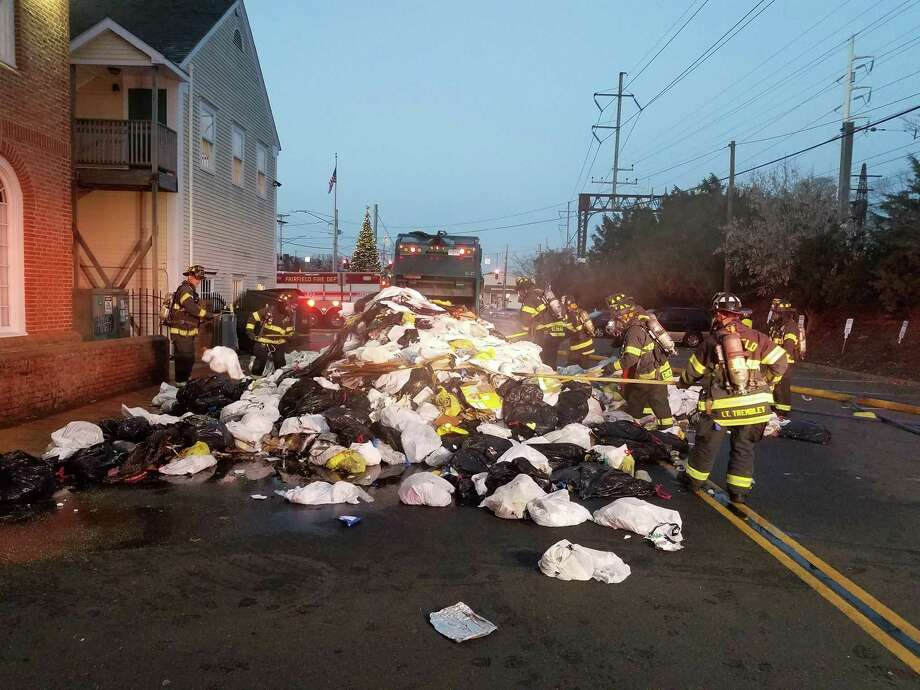 """A garbage truck caught fire in Fairfield on Thursday, Dec. 7, 2017. According to the fire department, """"the first arriving Officer, Lt Phil Higgins, instructed the driver to dump the flaming refuse into the road, an action which prevented the fire from extending to the vehicle. Crews from three engines, one heavy rescue and one command vehicle quickly brought the blaze under control. The truck driver who reported the fire was not injured."""" Photo: Fairfield Fire Department Photo"""