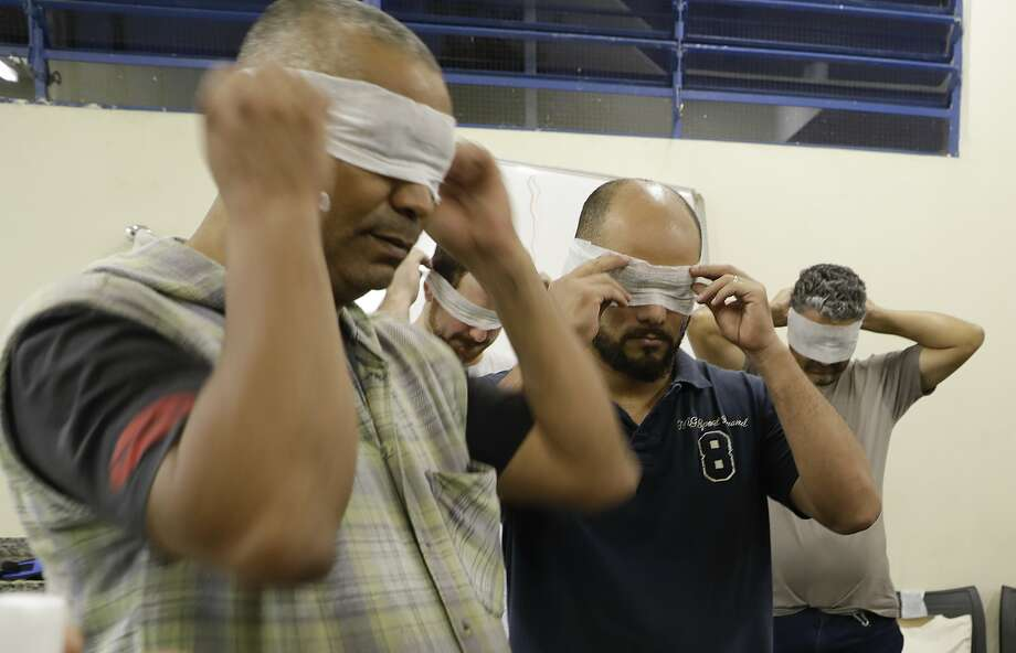 Members of the nonpartisan group Acredito are blindfolded as part of a team-building exercise to exchange ideas about their low-income community's needs in Sao Paulo. Photo: Andre Penner, Associated Press