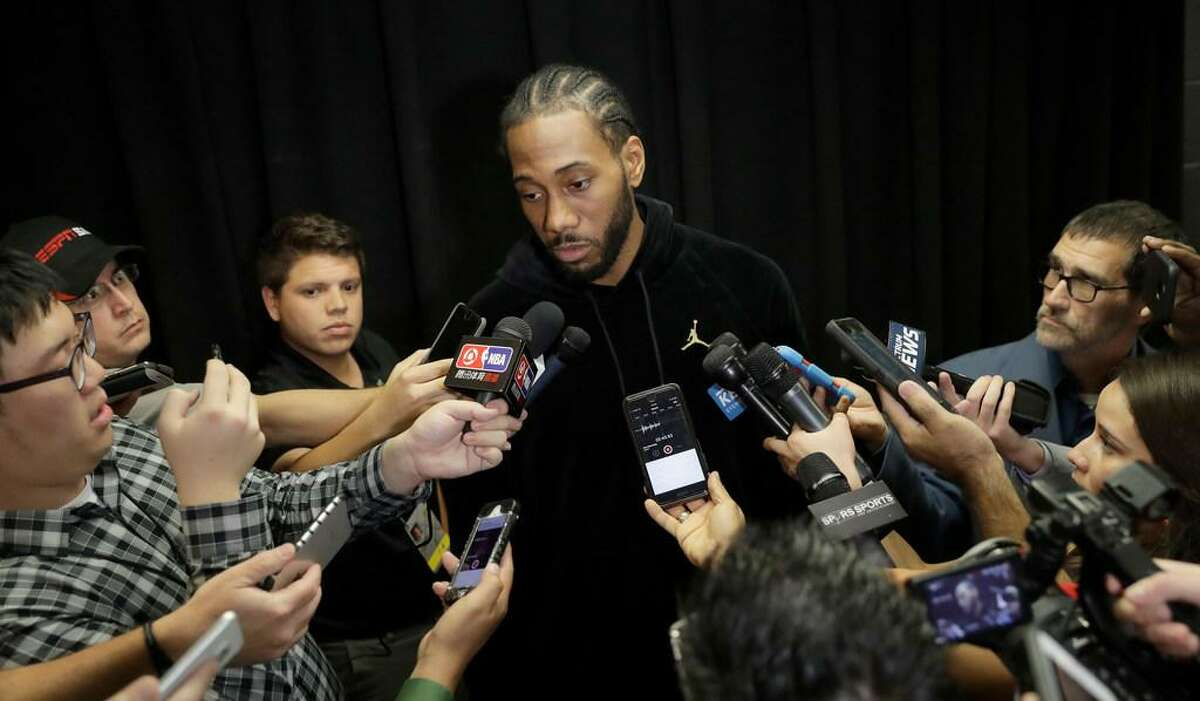 San Antonio Spurs forward Kawhi Leonard, who has not played this season due to an injury, talks with the media before an NBA basketball game against the Detroit Pistons, Monday, Dec. 4, 2017, in San Antonio. Leonard is expected to return to play soon.
