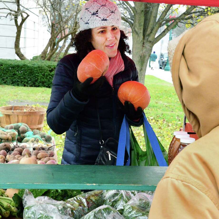 Katie Illouz of Niskayuna buys kabocha squash from Takacs Farm of Palatine Bridge at the Schenectady Farmers Market at City Hall Thursday Dec. 7, 2017 in Schenectady, NY.  (John Carl D'Annibale / Times Union) Photo: John Carl D'Annibale, Albany Times Union