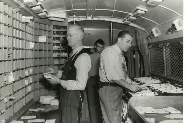Federally-owned postal bus stops in Midland on its mail route from Saginaw to Ludington. Seen here sorting mail is, left, Clyde Jones, Burton Stacey and George Campbell. The letter case is at left and the paper rack is at right. November 1949