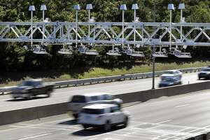 Cars pass under toll sensor gantries hanging over the Massachusetts Turnpike. Connecticut lawmakers have consistently rejected tolls and now the state's transportation fund is a year and a half from becoming insolvent.