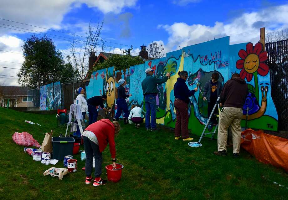 Volunteers work on restoring a mural defaced by graffiti at Greenwood Library Park on Sunday, Dec. 7, 2017. Photo: Courtesy Andrew Miller