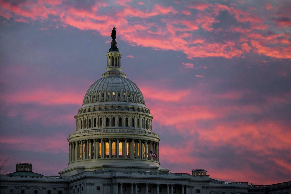 In this Thursday, Nov. 30, 2017, file photo, the sky over The Capitol is lit up at dawn as Senate Republicans work to pass their sweeping tax bill, in Washington. Congress' last major tax overhaul, three decades ago, was everything this years version isnt. The Tax Reform Act of 1986 won bipartisan support. Its benefits flowed more to low- and middle-income taxpayers than to wealthy individuals and corporations. And it added nothing to the federal deficit. None of that can be said for tax-cut package the Senate passed after the House approved a similar version.