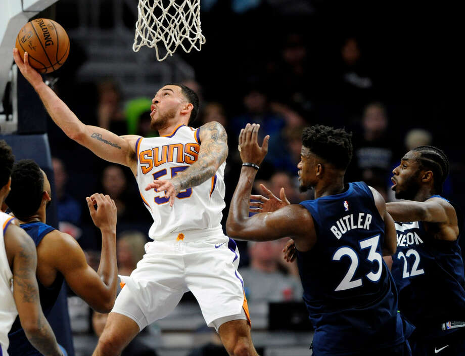 Phoenix Suns' Mike James (55) shoots against center Minnesota Timberwolves' Jimmy Butler (23) and Andrew Wiggins (22) during the fourth quarter of an NBA basketball game on Sunday, Nov. 26, 2017, in Minneapolis. The Timberwolves won 119-108. (AP Photo/Hannah Foslien)