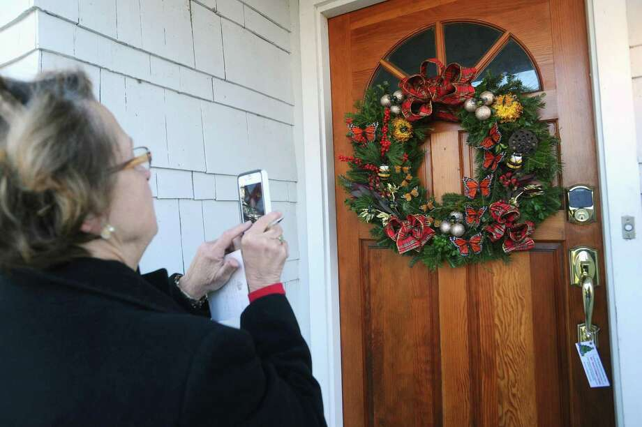 Clerk Janet McCabe takes a photo of a wreath before taking notes about the details while judging the newcomer category of the annual Doors of Shippan on Downs Avenue in Stamford, Conn. on Thursday, Dec. 7, 2017. Photo: Michael Cummo / Hearst Connecticut Media / Stamford Advocate