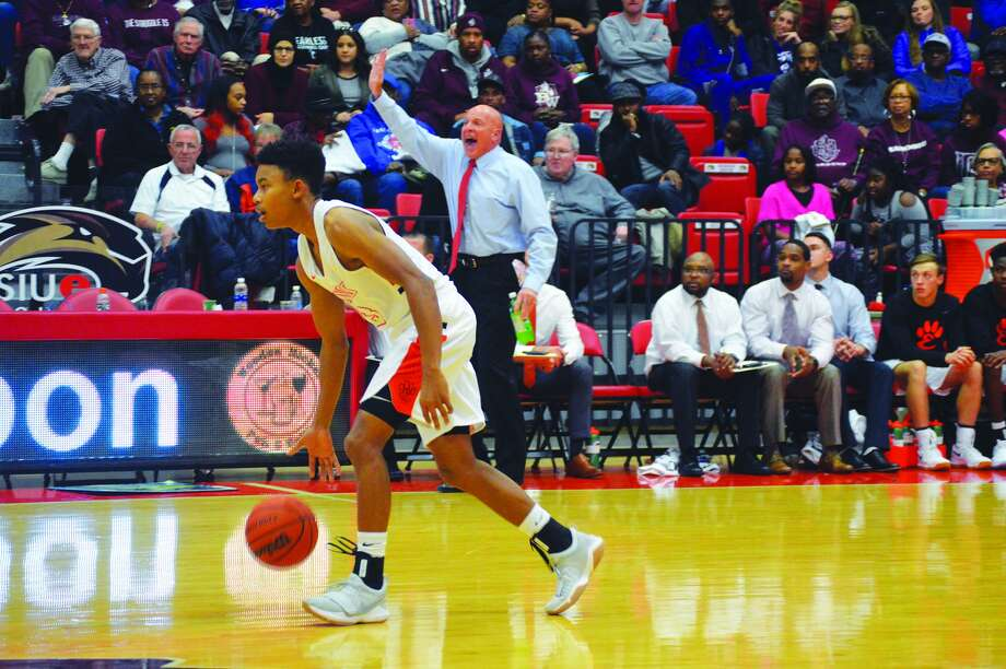 Edwardsville point guard Malik Robinson dribbles the ball up the court as coach Mike Waldo shouts out a play from the EHS bench during a game against Belleville West at SIUE.