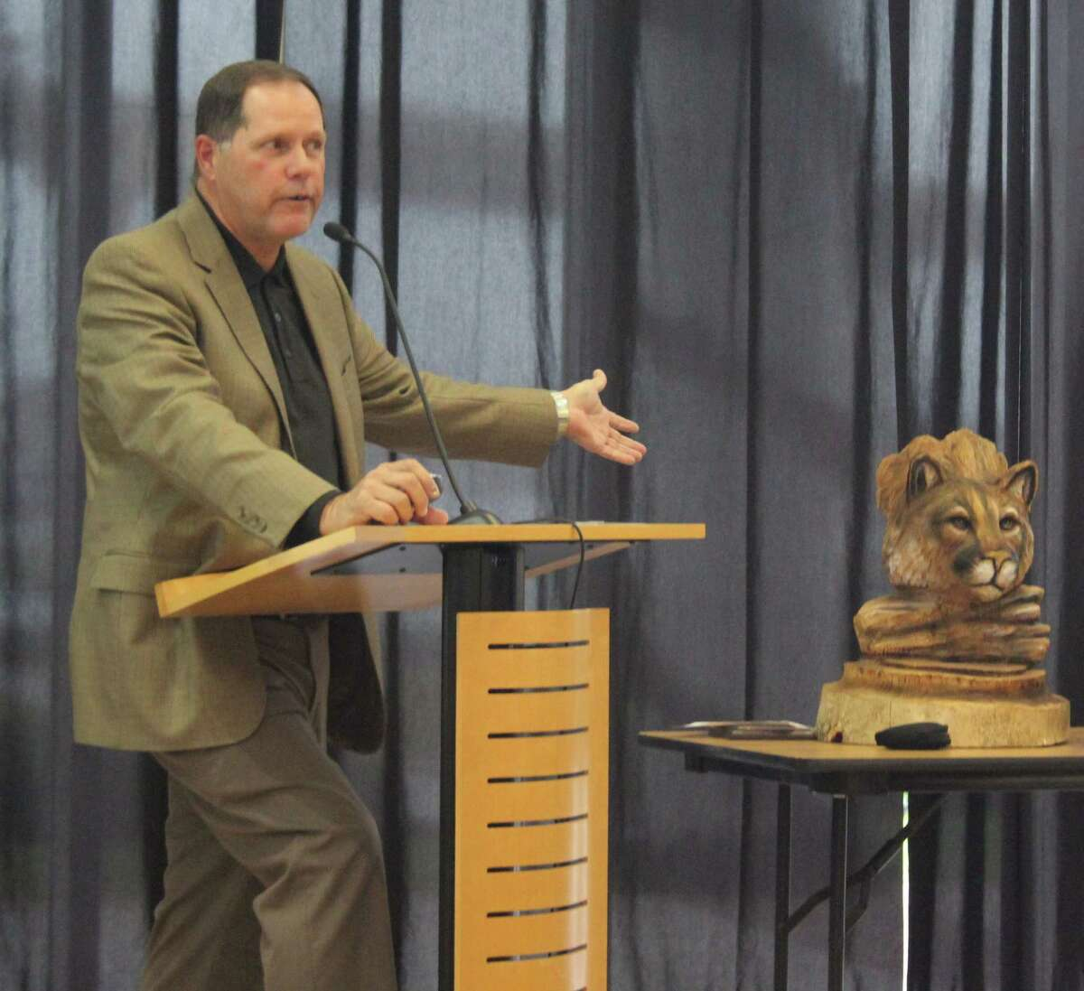 Greater East Montgomery County Chamber President Rick Hatcher displays a wood carving of a cougar, which was created by a chainsaw woodcarver at the Texas Sawmill Festival held on Nov. 11.